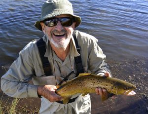 Legendary Australian actor and comedian, Garry McDonald, holding a nice sized brown trout he has just caught on fly.
