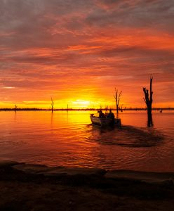 a fishing boat motors away from the shores of Lake Mulwala, Victoria, as the sunrise turns the sky blood red. © Fishotopia